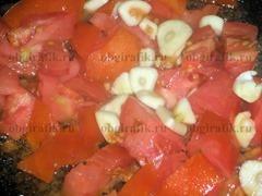6. Кубики помидоров обжаривают с пластинами чеснока.