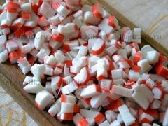 1. Крабовые палочки достать из упаковки, снять защитную пленку и нарезать небольшими кубиками.