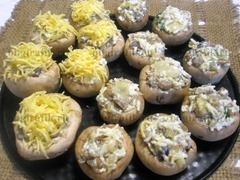 5. Полученным фаршем наполняют грибные шляпки, сверху присыпают сырной стружкой. Заготовки перекладывают в огнеупорную посуду и запекают в духовке 25-30 минут при температуре 180 градусов.