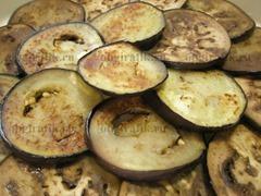 3. На отдельной сковороде также на растительном масле с обеих сторон обжаривают кольца баклажанов. Половину выкладывают на дно жаропрочной формы.