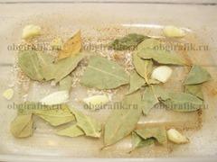 4. На дне формы раскладывают лавровые листы, бросают пару щепоток соли, перцев и рубленный чеснок.