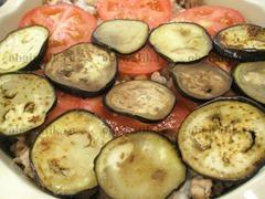 6. Выкладывают слой помидоров, нарезанных кругами, затем вторую половину баклажанов.