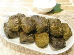 6. Подают долму с соусом из сметаны, чеснока и зелени, приправив солью с перцем по вкусу.