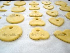 7. Раскатав охлажденное тесто в пласт толщиной 2-3 мм, вырезают фигурки. С одного края проделывают отверстие для нити. Переложив на противень с пергаментом, выпекают 15 минут при температуре 180 градусов.