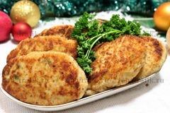 7. Зарумяненные куриные котлеты подают к новогоднему столу, украсив веточкой свежей зелени.