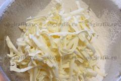 4. Добавляют натертое сливочное масло (предварительно заморозив), вымешивают руками до крошки.