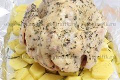 5. На картофельном «пьедестале» разместить птицу. Плотно упаковать в фольгу и отправить на 1 час в раскаленную духовку. Запекать при температуре 180 градусов.